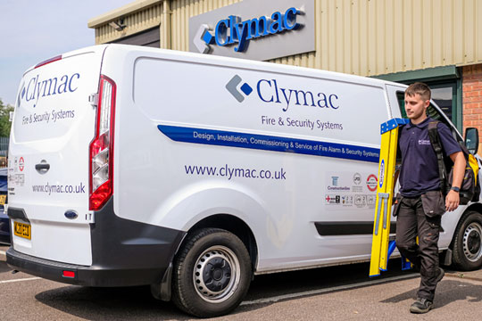 Clymac employee with step ladder next to company van.