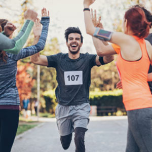 Man finishing a marathon while high fiving 2 people.