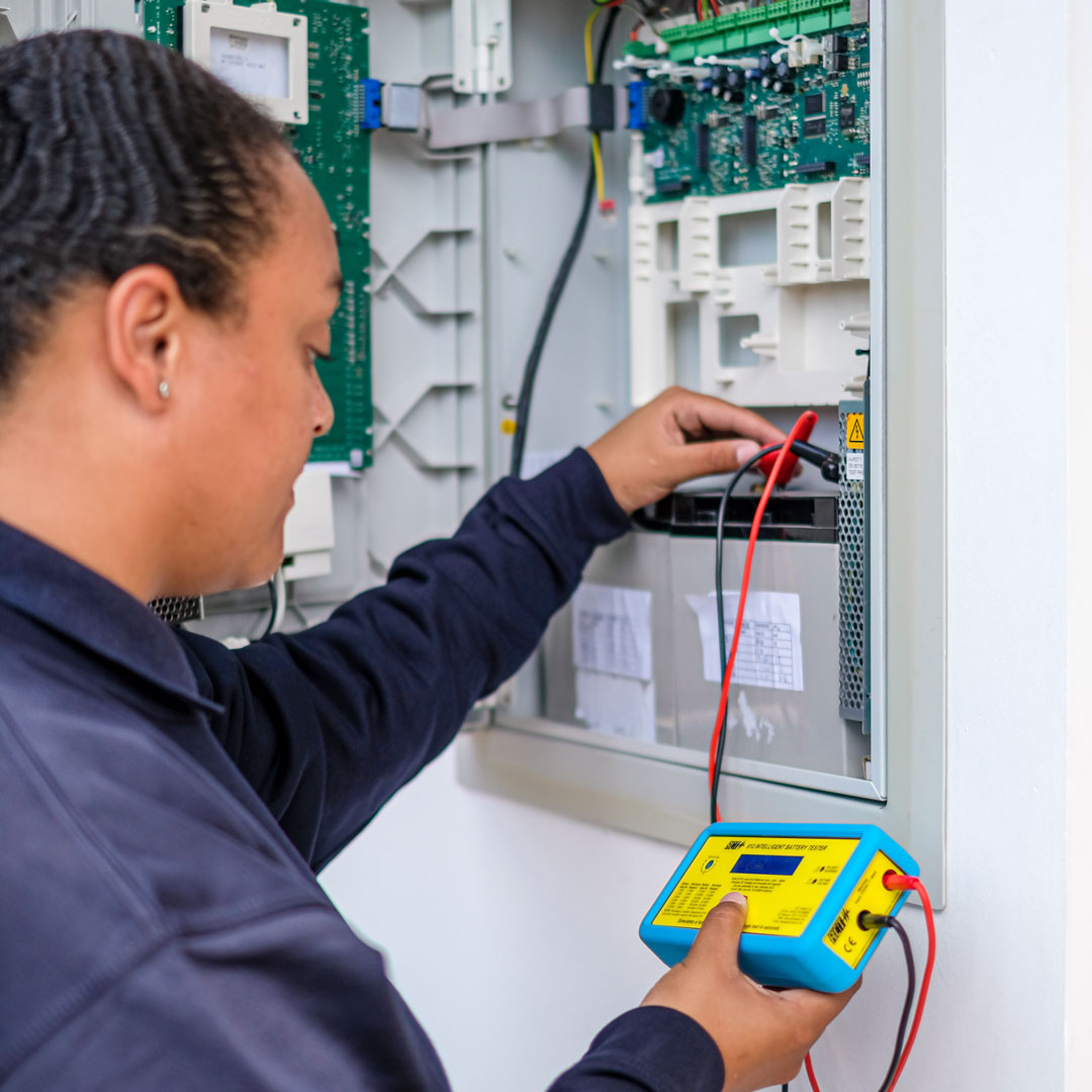 Woman electrician testing a device