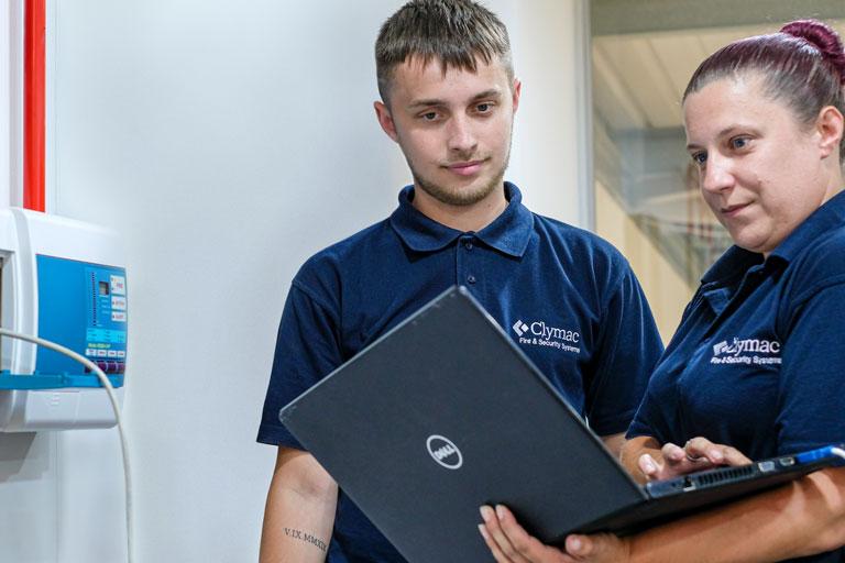 Woman employee showing man something on a laptop
